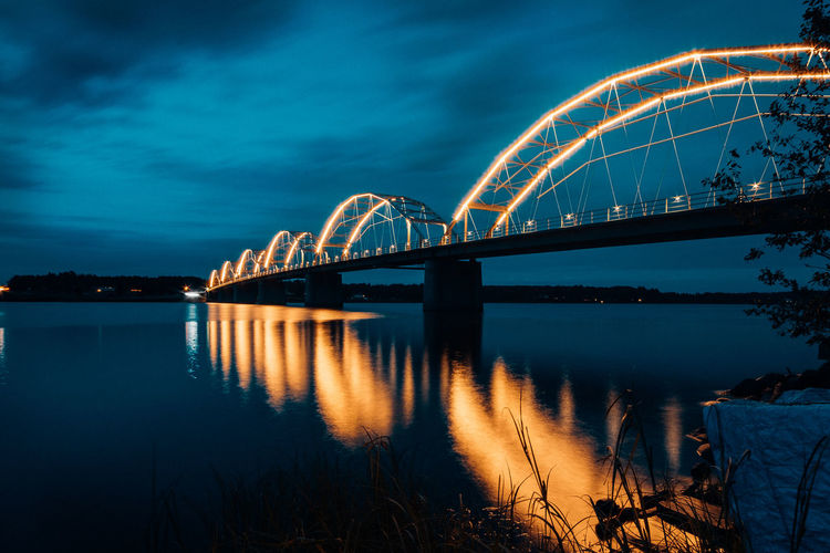 Low Angle View Of Illuminated Bridge Over River Against Sky At Night