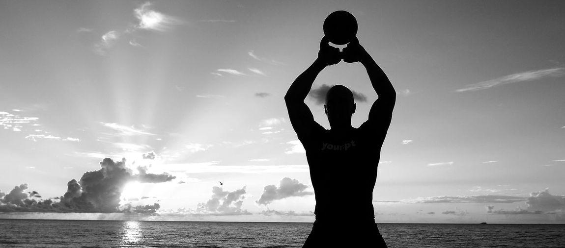 Silhouette Man Holding Kettlebell At Beach Against Sky During Sunset