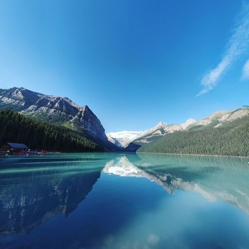 Reflection Of Mountains On Calm Lake Louise Against Blue Sky