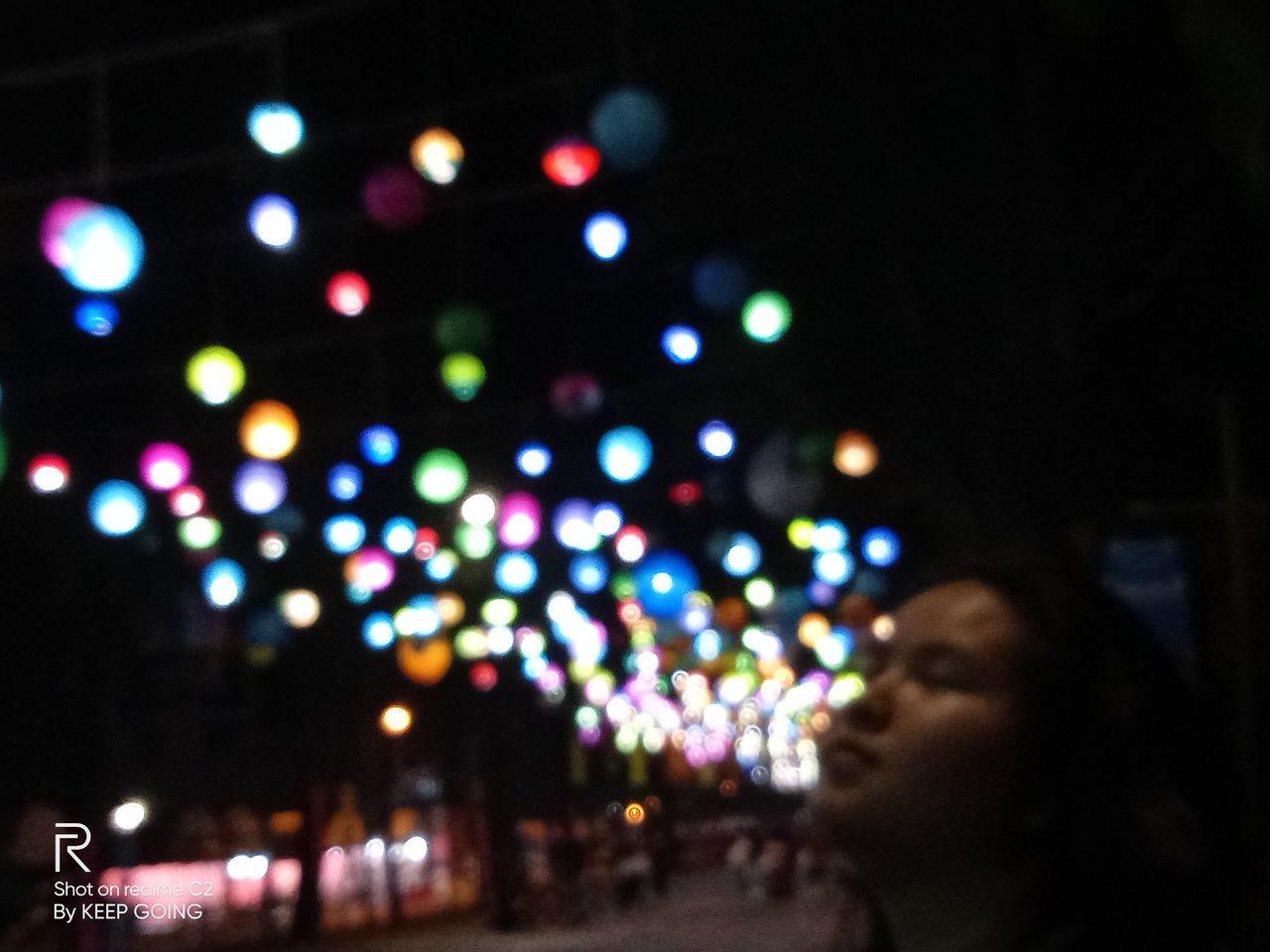 DEFOCUSED IMAGE OF WOMAN LIGHTS AT ILLUMINATED STREET LIGHT