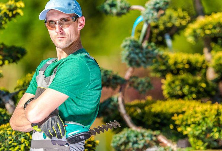 Portrait of gardener standing by plants