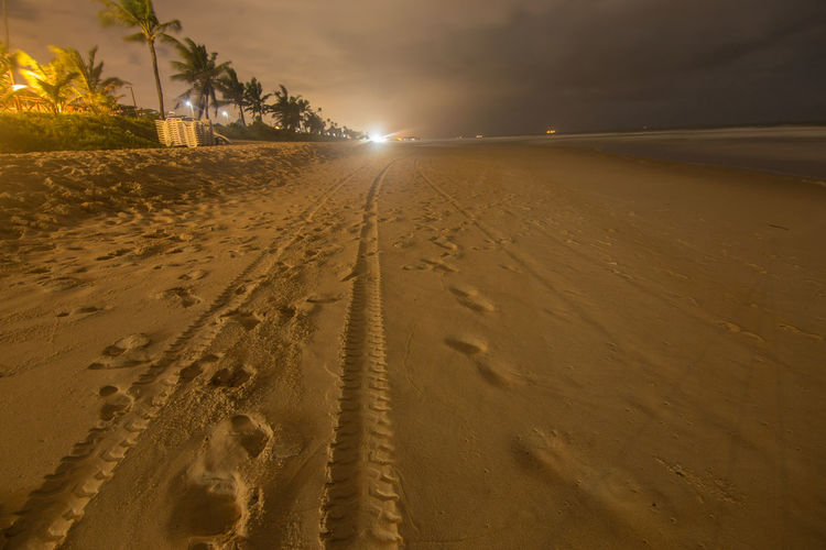 Footprints on sand at beach against sky at night