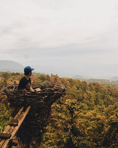 Young Man Looking At View While Sitting On Nest Against Cloudy Sky