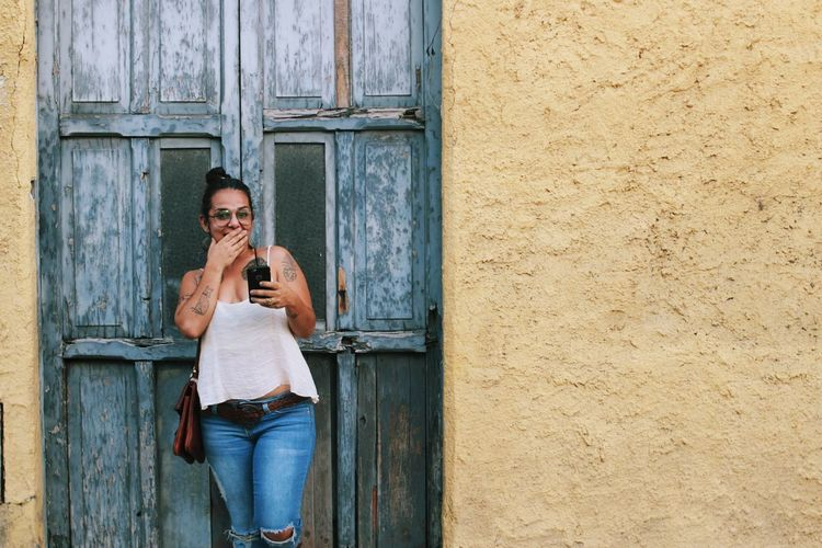 Portrait of young woman using mobile phone while standing at door