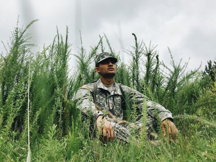Young Soldier Sitting On A Green Field