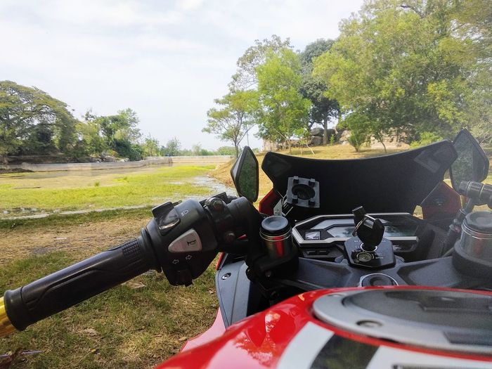 Close-up of motor scooter on field against sky