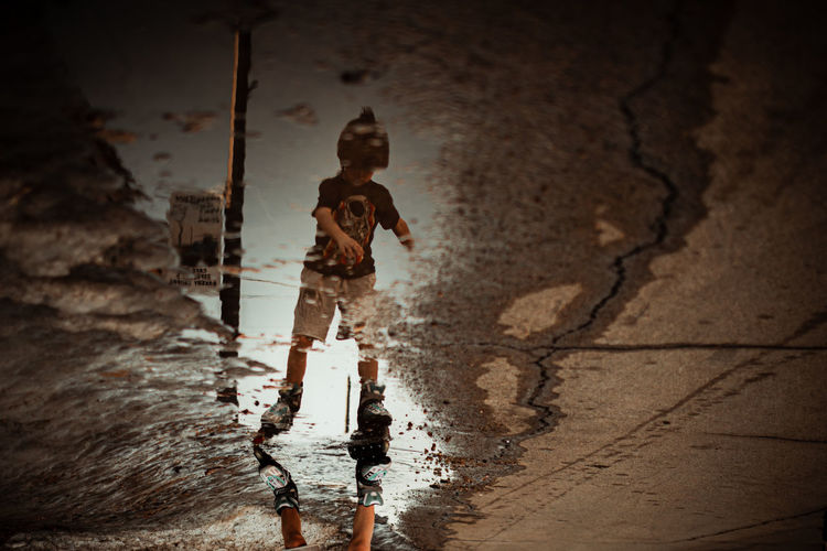 Reflection of silhouette man in puddle