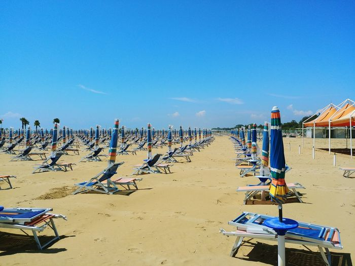 Chairs on beach against clear blue sky