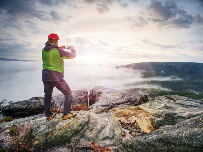 Traveler taking vacation photos of beautiful sunset in autumn nature by smartphone, holiday
