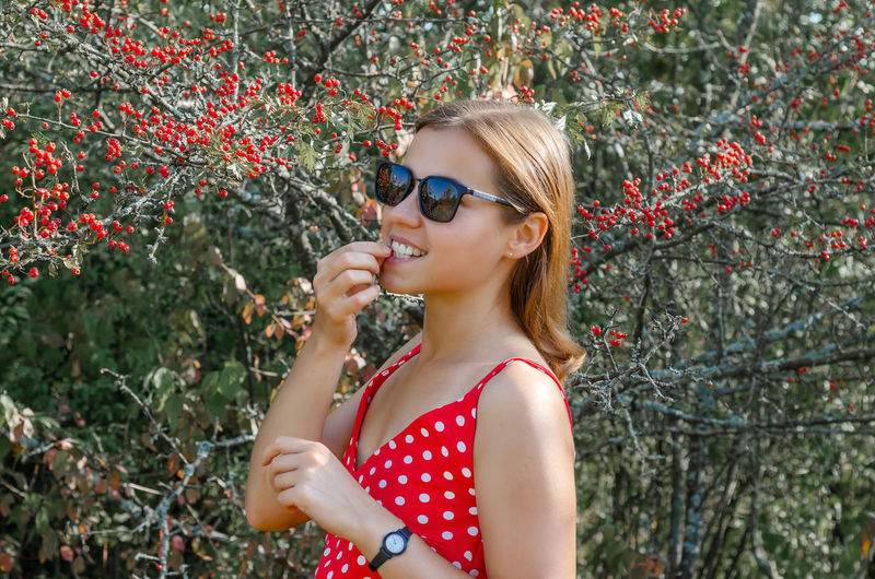 Midsection of woman wearing sunglasses against plants