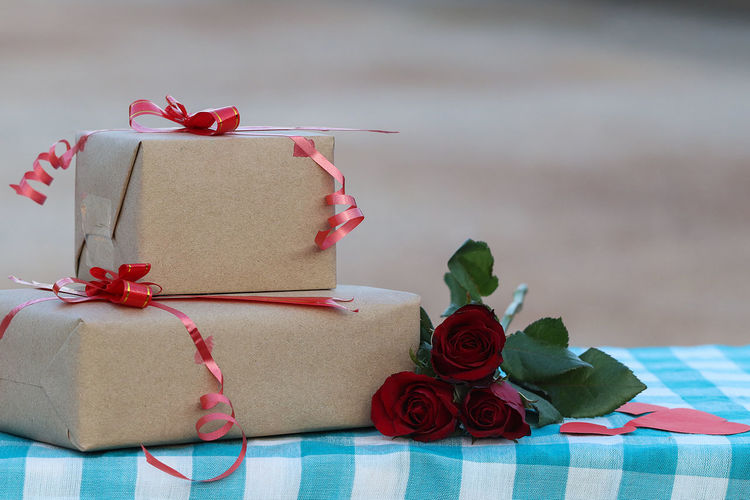 Close-up of gift boxes and roses on table