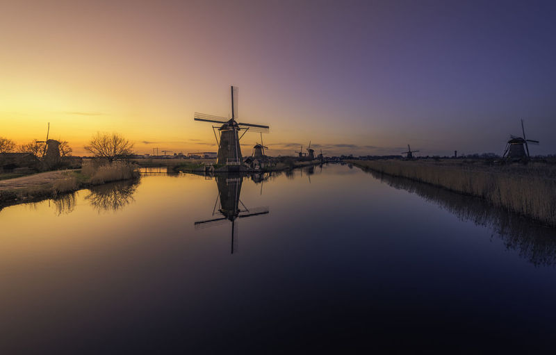 Lake By Traditional Windmills Against Clear Sky During Sunset