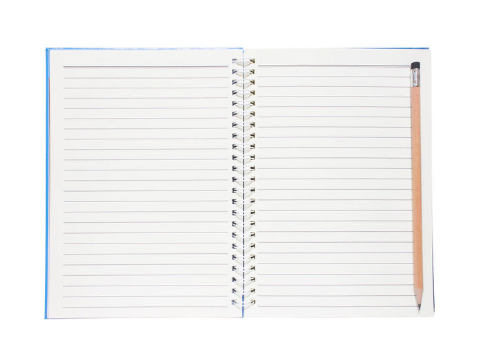 Directly above shot of open book with pencil against white background