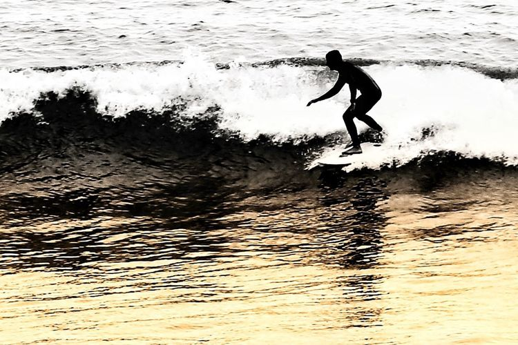 Silhouette man surfing in sea