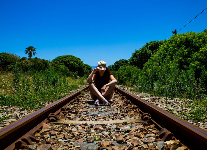 Woman standing on railroad track against clear blue sky