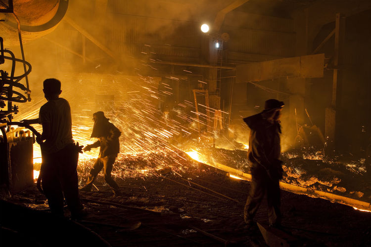 Steelworker at blast furnace Hard Work Hot Industry Steel Works Burning Flame Foundry Auxiliary Full Length Glow Glowing Hardhat  Headwear Heat - Temperature Illuminated Iron - Metal Men Occupation People Protective Workwear Real People Silhouette Standing Steel Mill Steel Worker Working