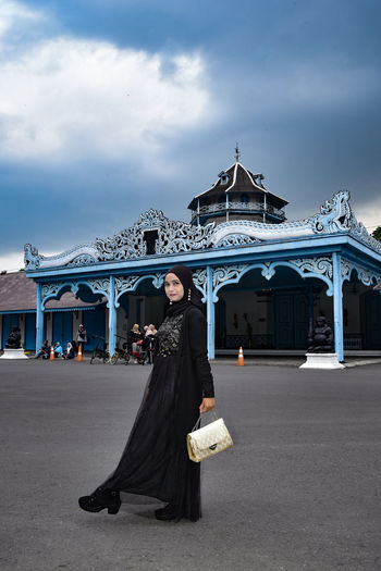 Full length portrait of woman standing against historical building