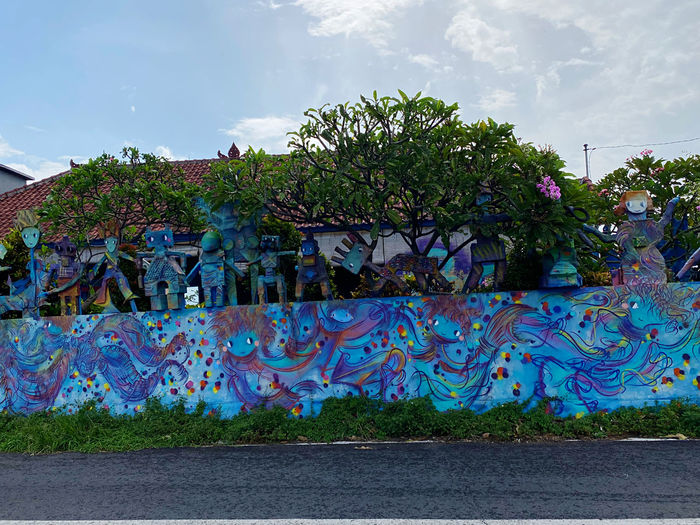 Graffiti on tree by plants against sky