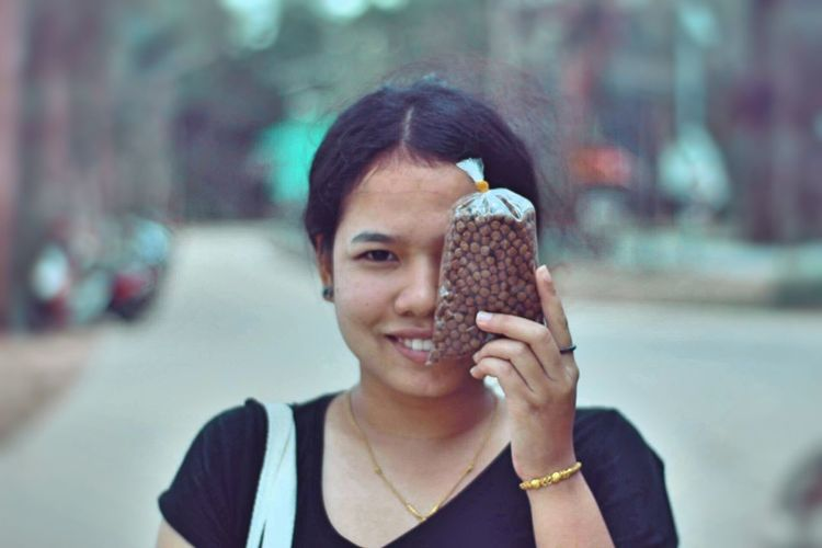Close-up of young woman holding packet