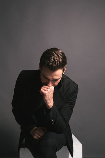 Young man looking away while sitting against wall