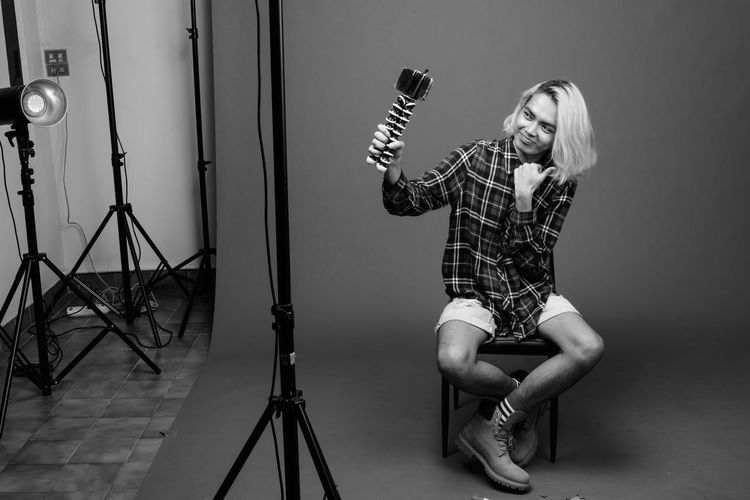 Full length portrait of young woman photographing
