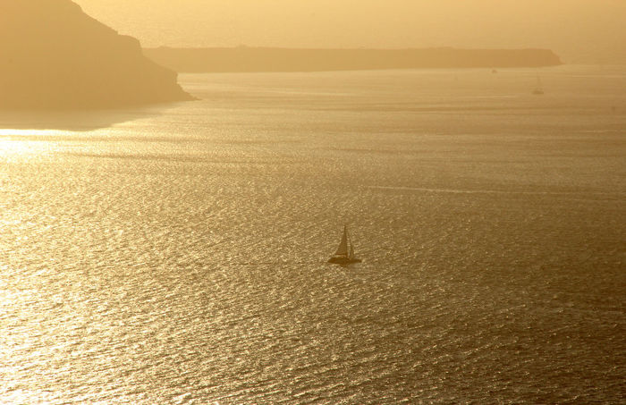 Sunset Sailing Santorini Beauty In Nature Boat Coastline Greece Greek Islands Holiday Horizon Over Water Idyllic Nature Nautical 43 Golden Moments Remote Sailing Sailing Boat Sailing Holiday Santorini Scenics Sea Seascape Tourism Tranquil Scene Tranquility Travel Destinations Vacations Water