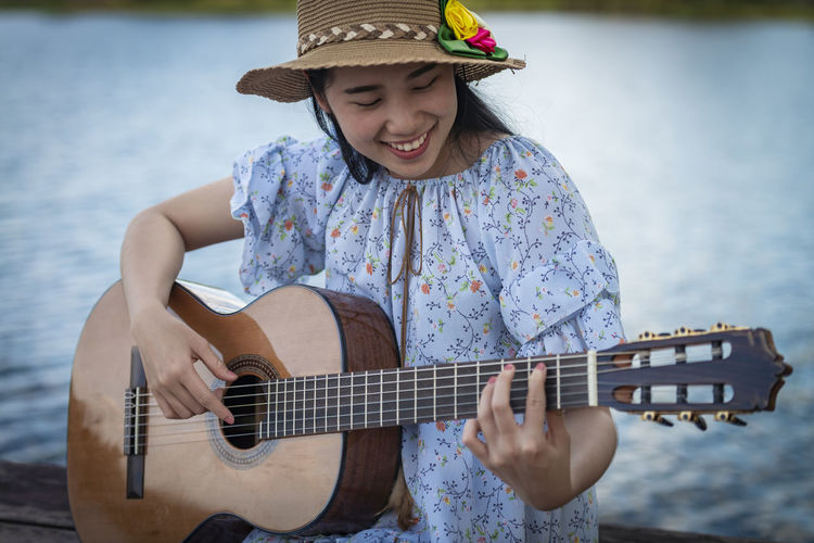 Portrait of woman playing guitar against water