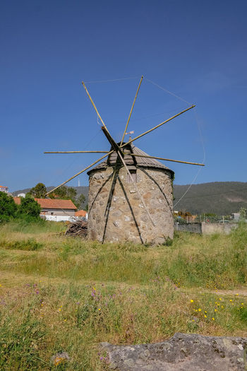 Traditional windmill on field against clear sky