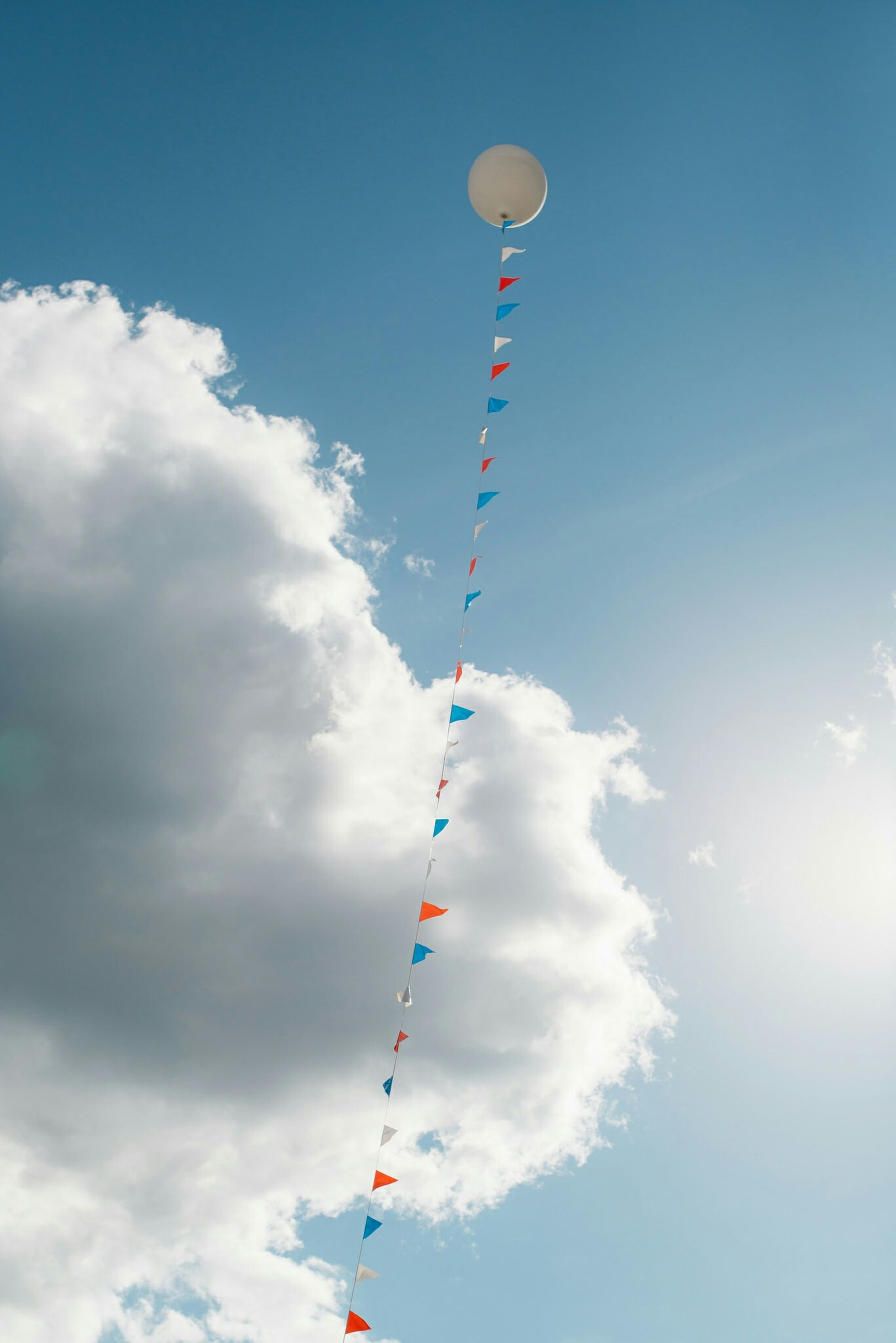 low angle view, sky, blue, cloud - sky, flag, street light, cloud, mid-air, identity, pole, transportation, multi colored, national flag, patriotism, day, outdoors, cloudy, flying, balloon, no people