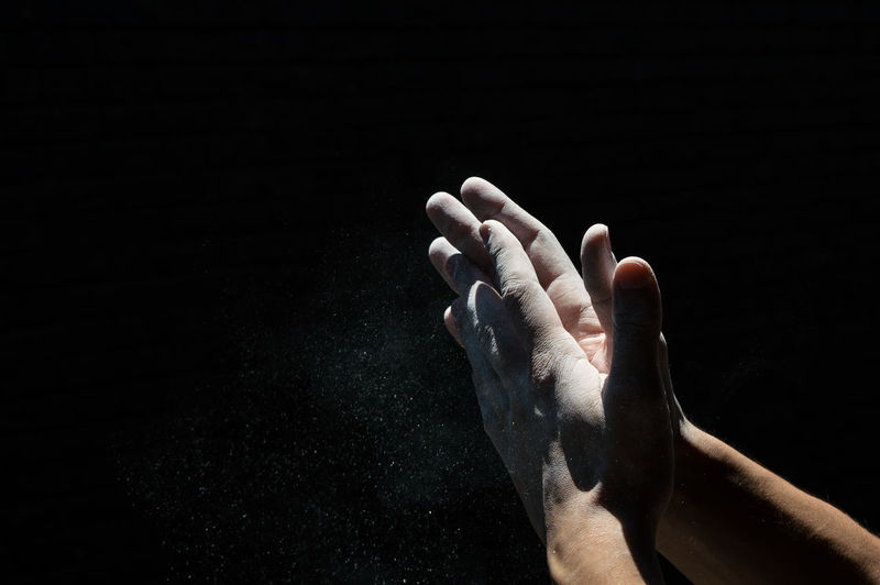 Close-up of cropped hands cleaning dust against black background