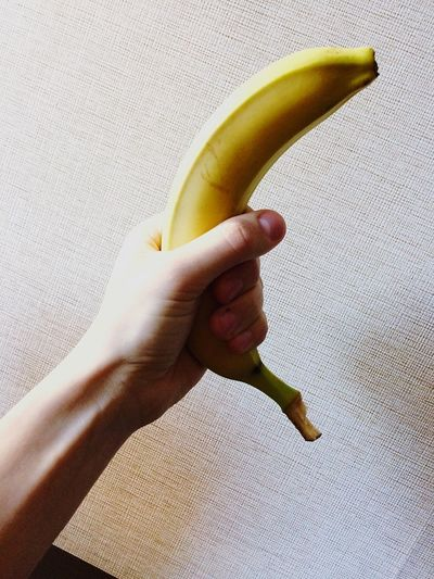 Close-up of hand holding banana against textile