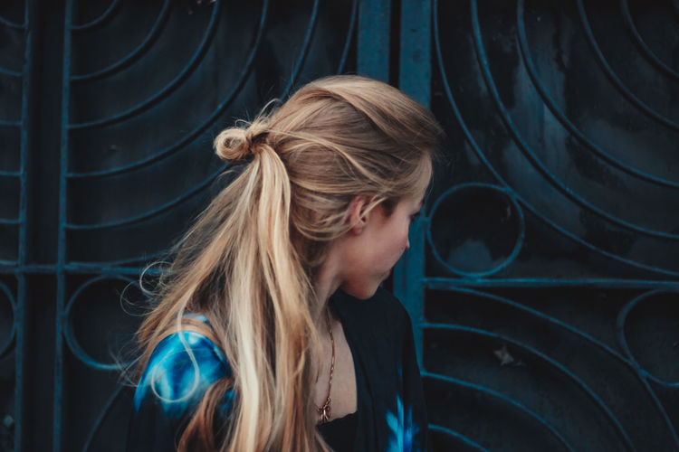 Close-up of woman looking away while standing against metal gate