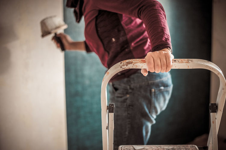 Midsection Of Man Standing On Ladder