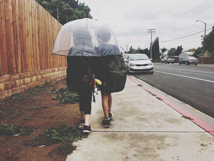 Rear View Of Backpack Siblings Walking Under Umbrella On Footpath