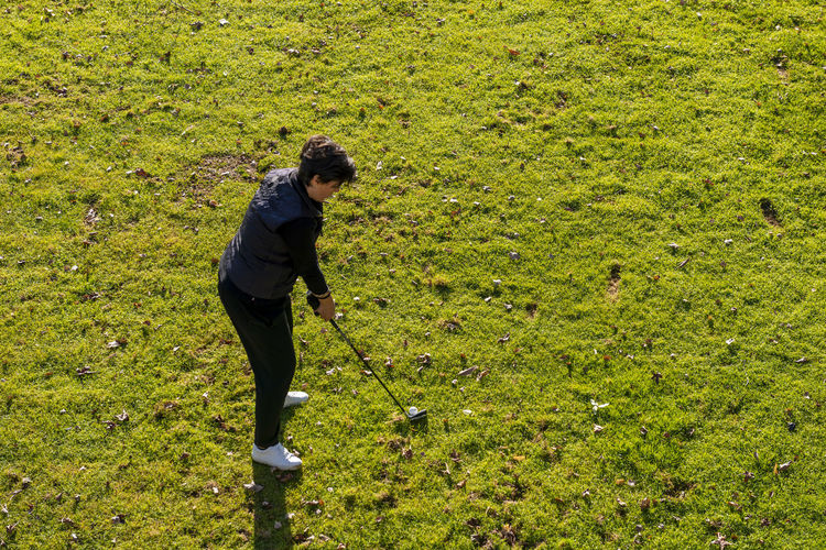 Aerial view on a golfer taking a shot on fairway.