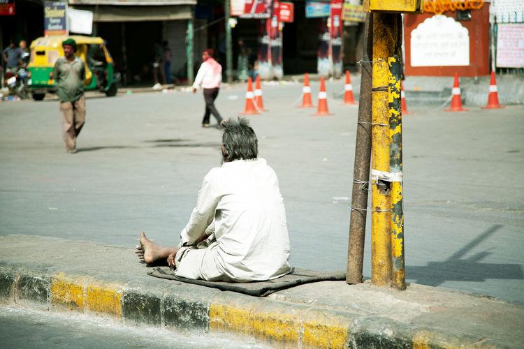Full length of beggar begging on road divider