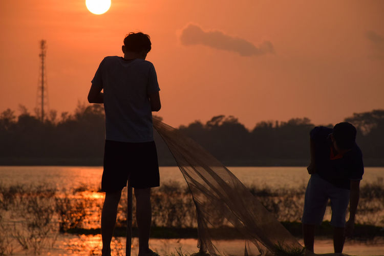 Rear view of silhouette mature men holding fishing net while standing by lake against sky during sunset