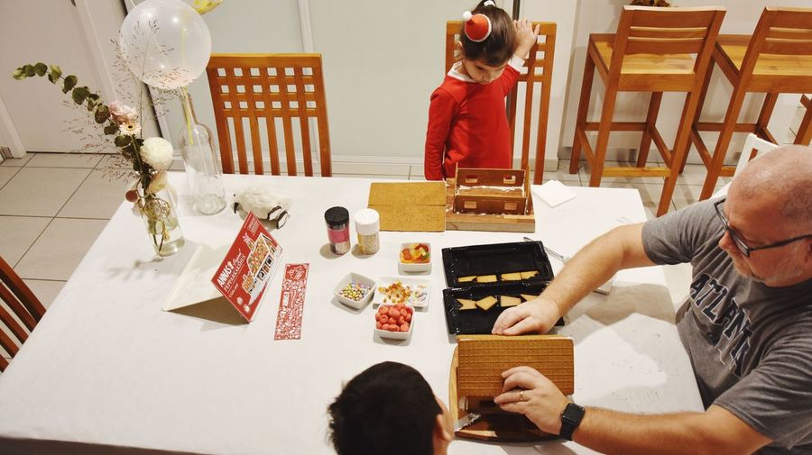 Gingerbread House Family Time EyeEm Selects Celebration Indoors  Table Christmas Event Men Decoration Holiday High Angle View Christmas Decoration Creativity Holiday - Event