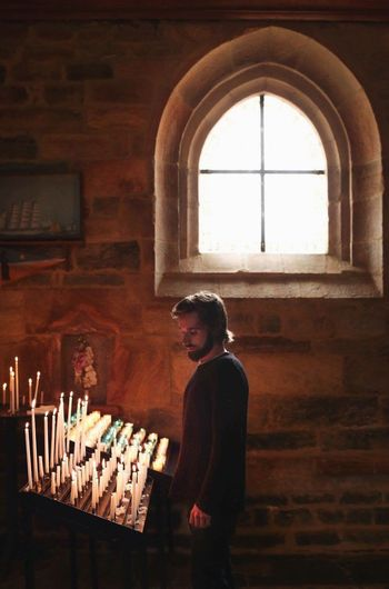 Side view of young man standing by candles in church