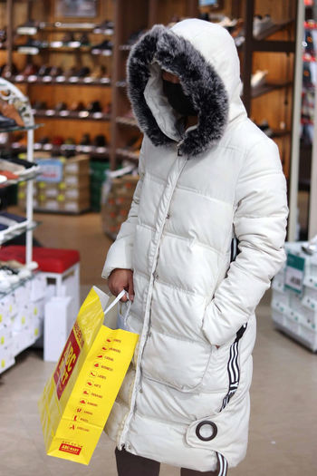 One Person Men Indoors  White Color Shopping Warm Clothing Adult Clothing Retail  Real People Yellow Color