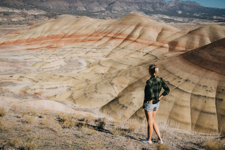 One Person Oregon Painted Hills, Oregon Painted Hills Pacific Northwest  Full Length Real People Land Mountain Landscape Scenics - Nature Leisure Activity Environment Adventure Standing Rear View Lifestyles Beauty In Nature Non-urban Scene Tranquil Scene Casual Clothing Day Outdoors Arid Climate Nature