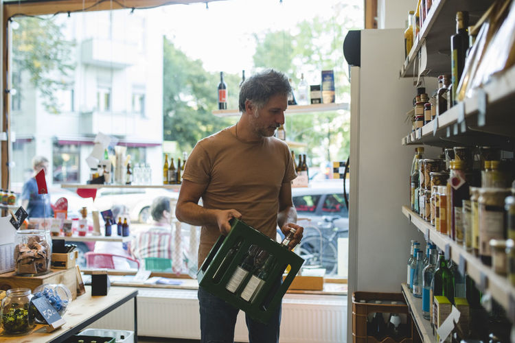 Mature salesman arranging bottle on shelf in deli