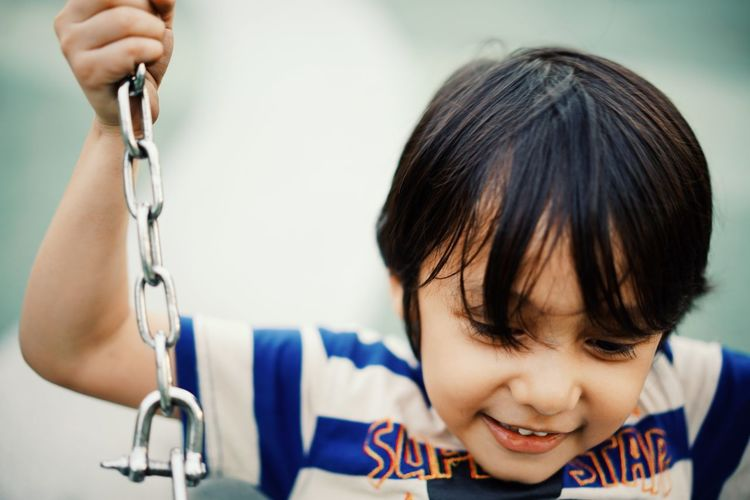 Close-up of smiling boy swinging in playground