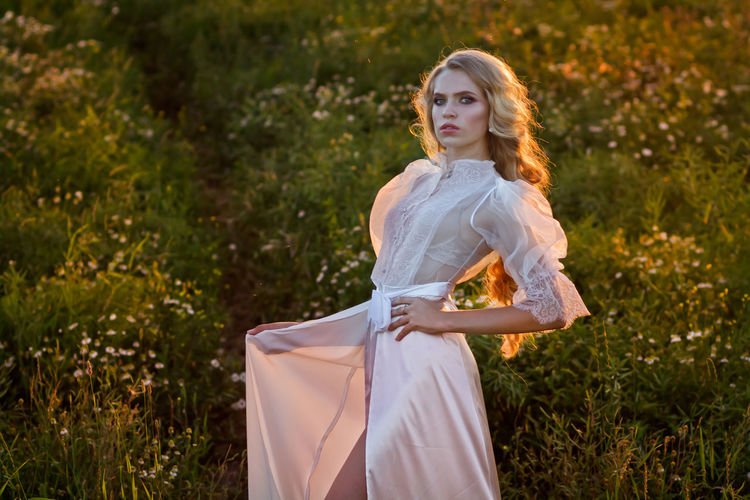 Beautiful young woman wearing white dress while standing on land at sunset