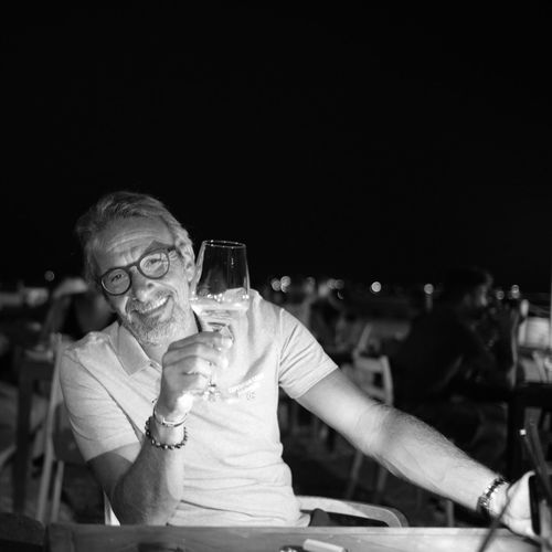 Portrait of happy man having wine in glass while sitting at outdoor restaurant during night