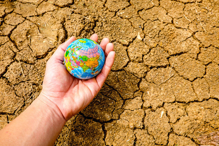 Cropped hand of person holding globe over dry field