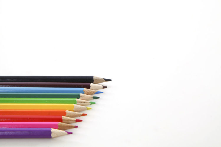 Close-up of multi colored pencils over white background