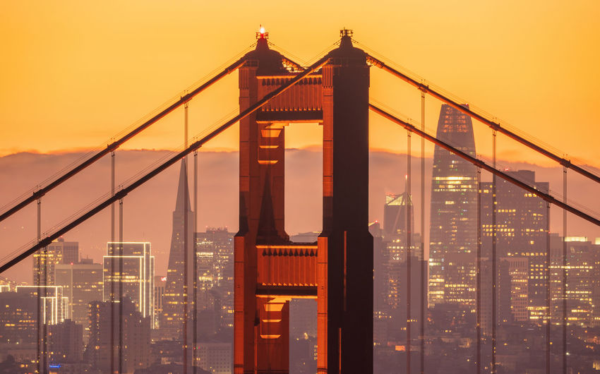 View of suspension bridge in city against sky during sunset