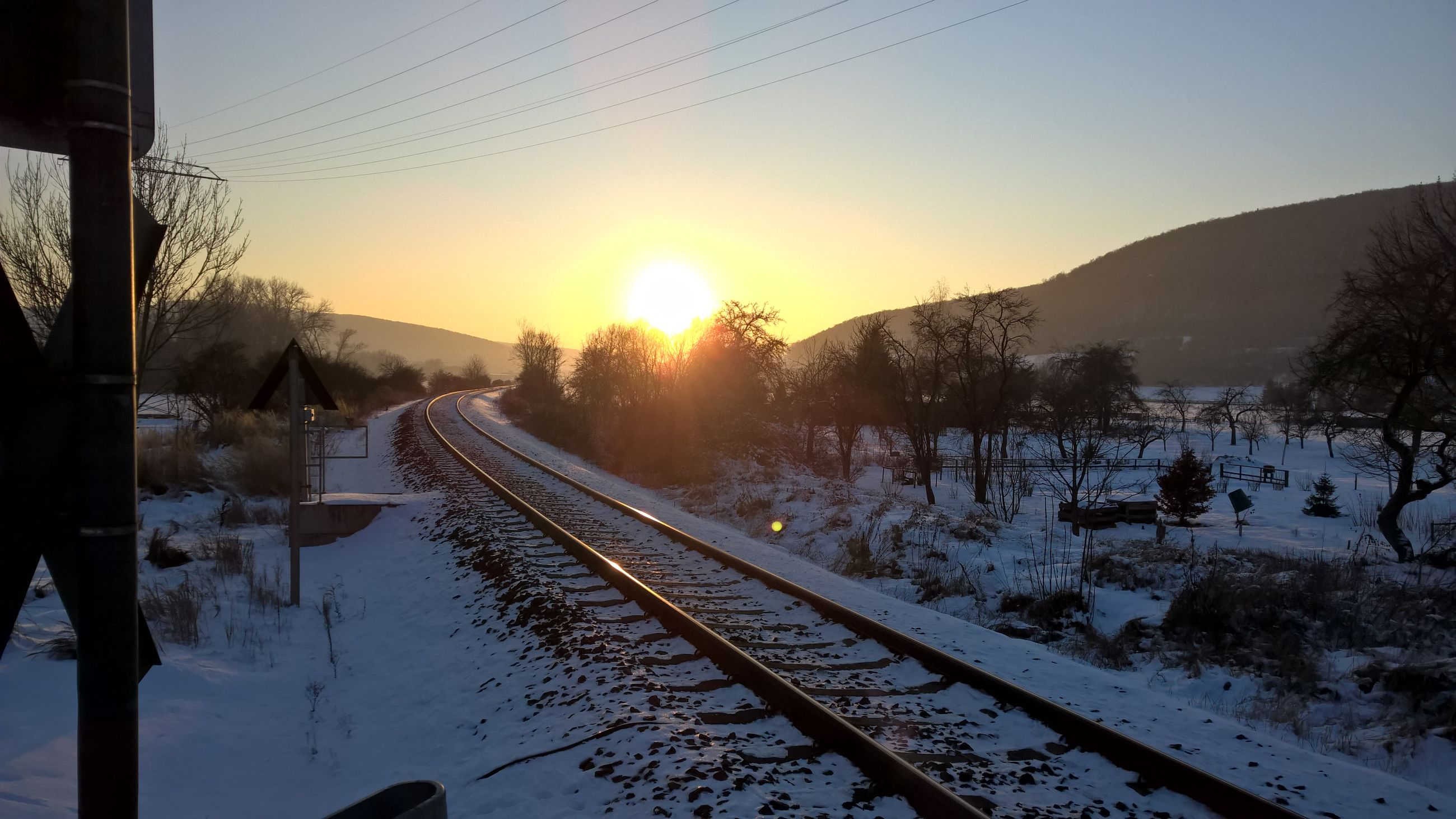 cold temperature, transportation, sunset, winter, sky, sunlight, snow, rail transportation, mode of transport, nature, beauty in nature, sun, no people, land vehicle, outdoors, tree, day