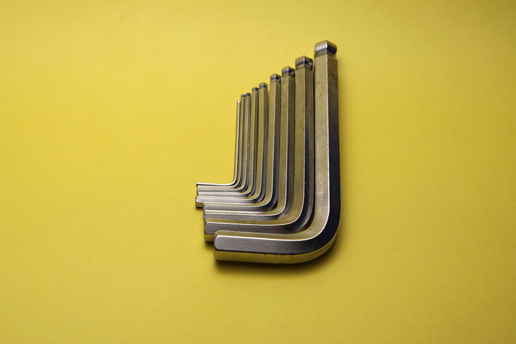 Directly Above View Of Silver Hex Wrenches Against Yellow Background